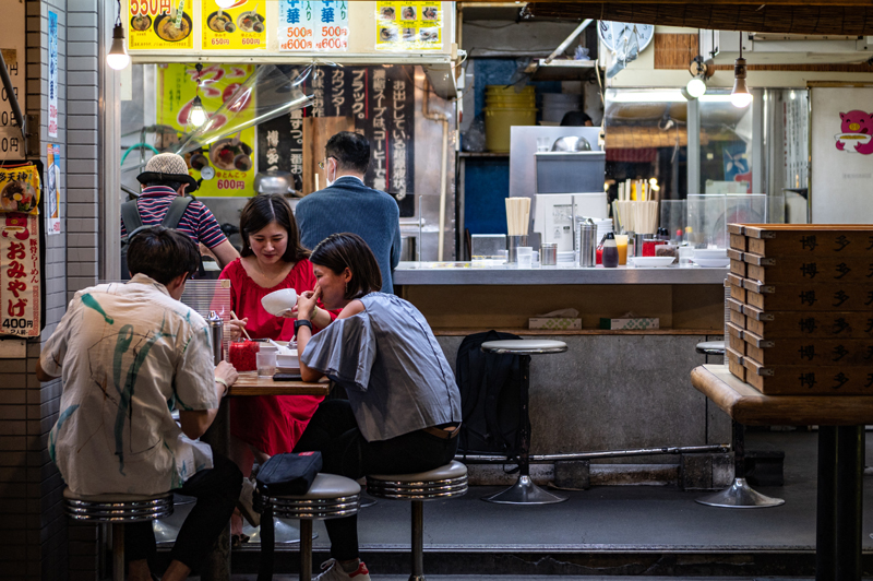 Diners eat at a restaurant in Shibuya district of Tokyo on August 1, 2021. AFP
