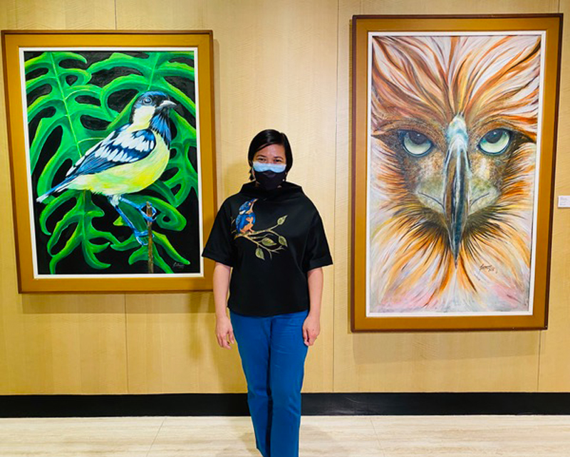 Artist and PhilFAS founder Bing Famoso stands between her two acrylic on canvas masterpieces: 'Ang Pardaliparus elegans at ang Alocasia portei' (left) and 'Banoy Philippine Eagle' (right) priced at P100,000 and P150,000, respectively.