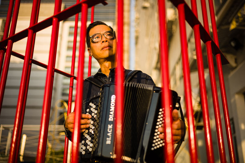 """This file photo shows local artist Kacey Wong playing the accordion inside a red mobile prison artwork called 'The Patriot,' a protest performance art project protesting against the National Anthem Law, at his studio in Hong Kong. Wong, one of Hong Kong's best known artists, confirmed that he had moved to Taiwan in search of """"100 percent freedom"""" from China's crackdown on dissent. AFP"""
