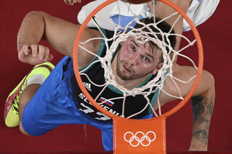 Slovenia's Luka Doncic and Argentina's Patricio Garino (top) fight for a rebound during the men's preliminary round group C basketball match between Argentina and Slovenia of the Tokyo 2020 Olympic Games at the Saitama Super Arena in Saitama.