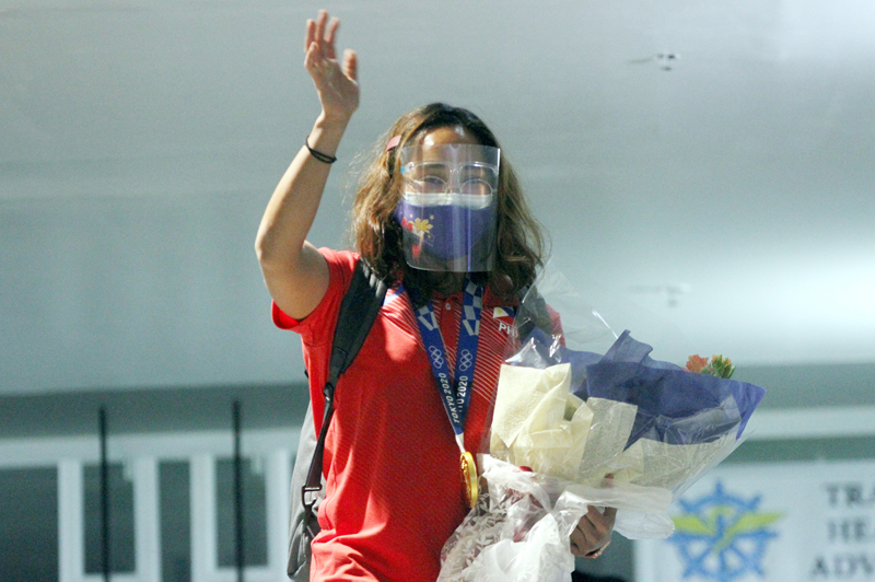 Hidilyn Diaz waves to well wishers upon her arrival at the NAIA Terminal 2.