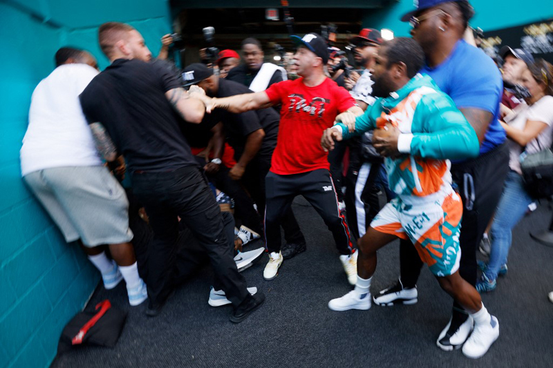 Floyd Mayweather and Jake Paul scuffle after the youtube star took the boxer's hat during a media availability drumbeating their fight at the Hard Rock Stadium in Miami Gardens, Florida.  AFP